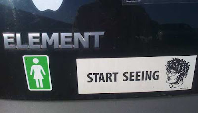 Black and white bumpersticker on a black car. It says START SEEING followed by a drawing of a bespectacled man with a funny hairdo