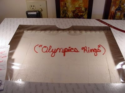 White cake with red letters that say quote Olympic rings unquote