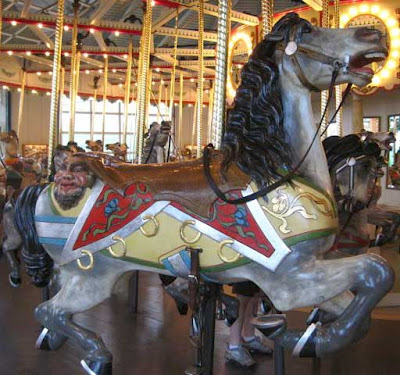 Carousel horse with a face in bas relief off the end of its saddle