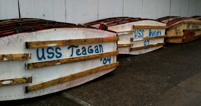The boat bottoms have names like USS TEAGAN 2004 spraypainted on them