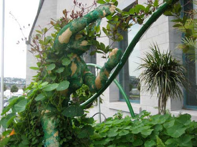 A green sculptural figure covered with plants