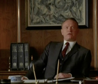 Mad Men's Lane Pryce at his desk with the three-volume OED in the background