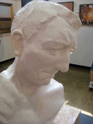 White plaster sculpture of a man's head, looking downward