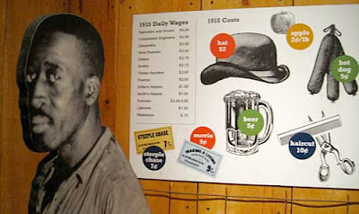 Black and white cutout photo of a black man looking into the camera, next to a sign showing images and prices