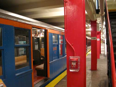 Red and blue wooden train car next to a subway platform