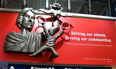Red billboard with metal bas relief sculpture attached of Lady Justice holding her scales, but instead of weights there are round rings attached and a boy is dangling from the rings