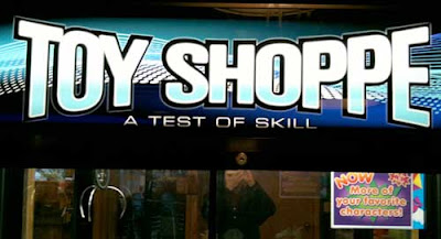 Lit sign reading Toy Shoppe, A Game of Skill in sans serif type