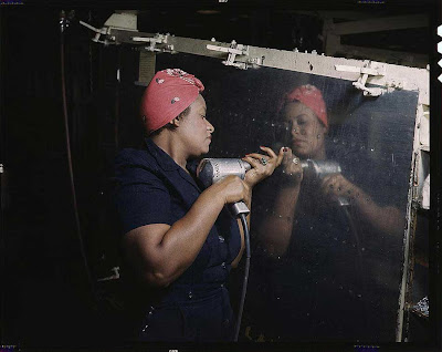 African American woman in a blue jumpsuit and red headscarf riveting a reflective metal panel