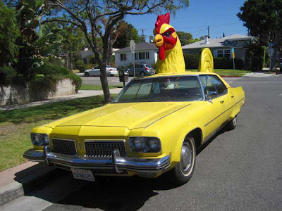 Yellow Cadillac with a yellow and red rooster atop it