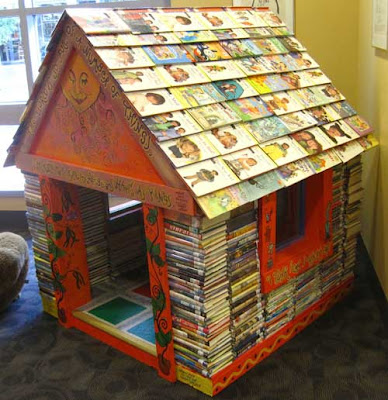 Miniature house made out of stacked books, with books for shingles on the roof