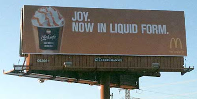 McDonald's billboard with photo of beautiful whipped cream and caramel topped paper cup and headline Joy. Now in Liquid Form