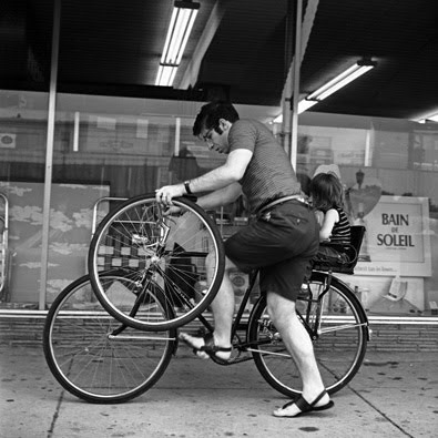 60s photo of a young man mounting a bike with an extra wheel in his hand, young child sitting in seat on back