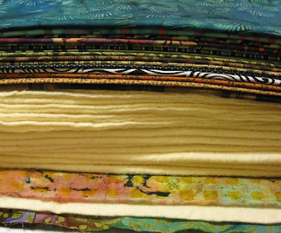 Stack of fabrics and batting to be quilted