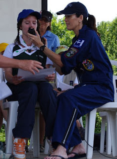 photo by Kim Mackrael, Guelph Mercury. Megan Sumner, a guide from Whitehorse, Yukon, is assisted Friday at Guelph Lake by Lori McFarlane of the space station amateur radio program as she asks astronaut Doug Wheelock a question.