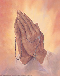 Cross with rosary beads in the hands of praying man photo