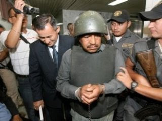 Abraham Lancerio Gomez in helmet and handcuffs, in a crowd