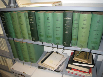 Library bookshelves with many volumes of a Braille Bible