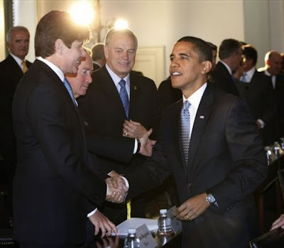 Barack Obama shakes the hand of indicted Governor Rod Blagojevich on December 2, 2008. Mitch Daniels is in the background.