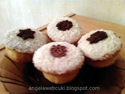 Kókuszpudingos muffin, vanília pudingos kókuszreszelékes töltelékkel, fehér csokoládéval, kókuszreszelékkel és csoki lapkákkal lefedve.