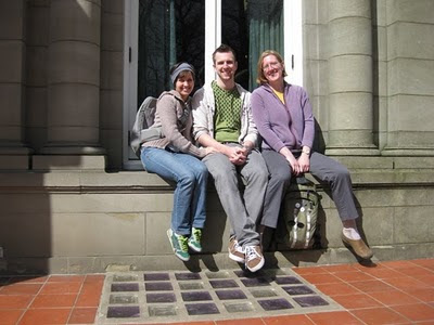 Color photo of Renee, Brian and Anna on the window ledge of a bay window at Pittock Mansion museum, Portland, Oregon. Automatic timer photograph by Renee Hartig.