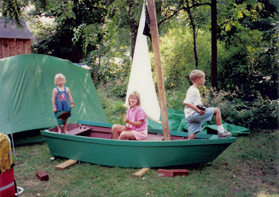 three children on a sailboat in the grass