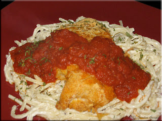 coated parmesan chicken  with roasted tomato sauce on spaghetti