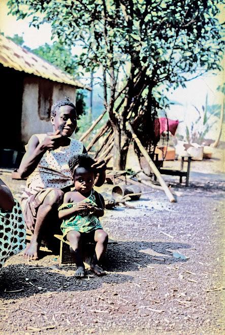 Bonya plaiting Baby Hokey's hair - Kenema