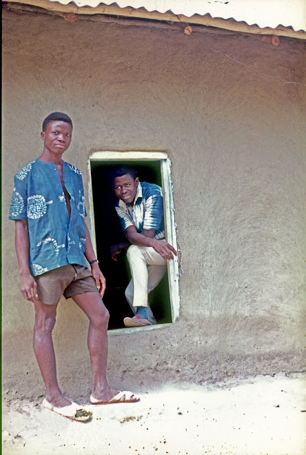 Sam Allie in doorway with friend at village near Kenema