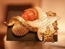 Anello realizzato in oro,corallo e madreperla su base in ebano