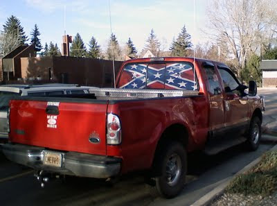 Large red truck, confederate flag in back window, two skull and crossbones bumperstickers, one bumpersticker saying 'Bad ass boys drive bad ass toys,' and one unreadable sticker