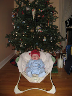 in front of the tree wearing a silly hat