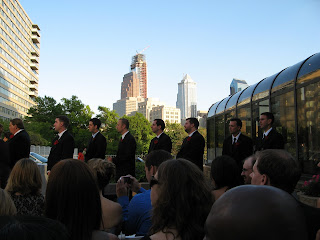 a row of handsome men with the city skyline behind us