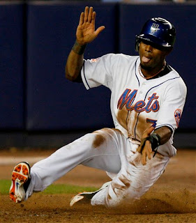 Jose Reyes claps while scoring on an errant throw