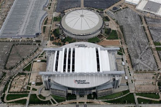 Reliant Stadium's roof is missing a few pieces.  That's the Astrodome next to it