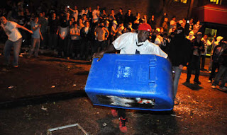 A Penn State fan ironically tries to steal a newspaper box.  Ironic because he doesn't know how to read