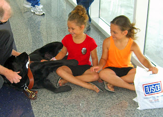 Photo of Blaze comforting two young girls who just bid their father goodbye