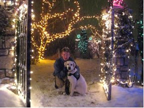 Franco pictured with his puppy raiser seated in the snow with Christmas lights all around