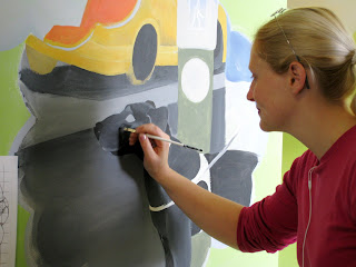 Artist Michelle Imbach painting on details of a black lab