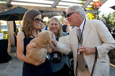 George Thompson, with his wife Margot, greet a Golden Retriever puppy held by GDB staff member Denise St. Jean.