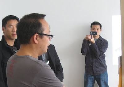 Jimmy J. Aquino takes a digital video of Jeff Yang giving a Secret Identities slide presentation. Photo by Giant Robot.