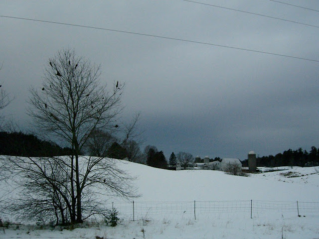 Snow-covered field in New Hampshire with a house and silo.
