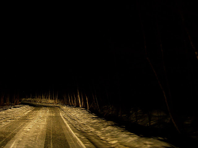 Icy New Hampshire road at night, illuminated by headlights.