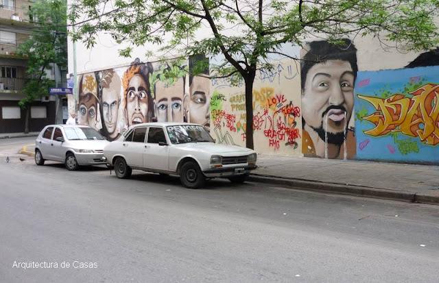 Mural artístico intervención urbana caras expresivas pintadas en Buenos Aires