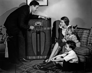 vintage photo of family gathering around radio
