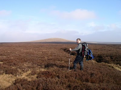 Matt trekking through the heather to the remote summit of Meugher in Nidderdale