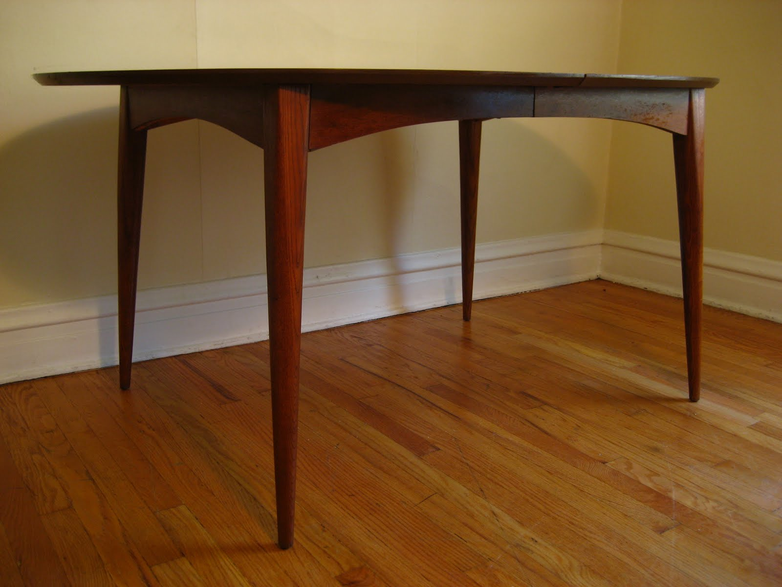 Mid century modern dining table with leaf - Mid Century Modern Dining Table Oval Shaped Dining Table With Internal Leaf System Arched Cross Bracing And Tapered Legs Highlight This Walnut Table