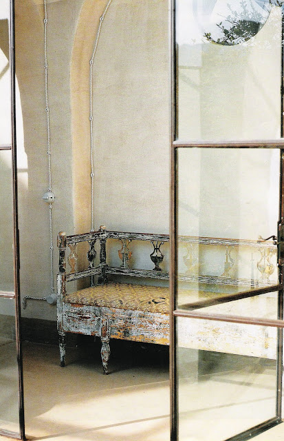 Aged paint finish on carved wood bench, simple iron and glass doors, image via Elle Decor Italia as seen on linenandlavender.net