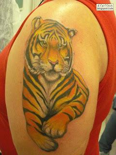 Tigre tatuado no braço.