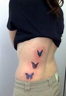 Três borboletas tatuadas na parte lateral das costas