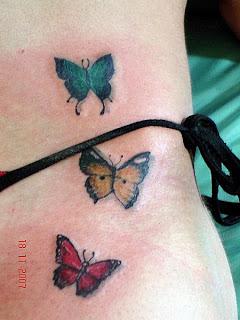 Três borboletas tatuadas na região do quadril